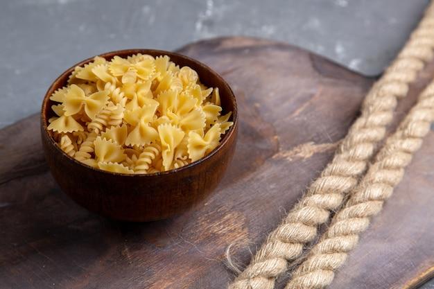 Une vue de face des pâtes italiennes crues peu formé à l'intérieur de la plaque brune sur la table brune pâtes italiennes repas