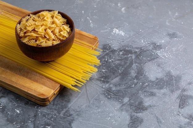 Une vue de face des pâtes italiennes crues peu et longtemps formé à l'intérieur de la plaque brune sur la table grise des pâtes italiennes repas