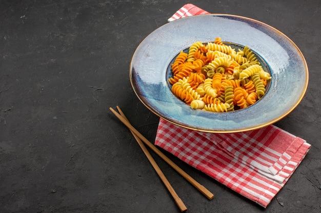 Vue de face pâtes italiennes cuites pâtes en spirale inhabituelles à l'intérieur de la plaque sur l'espace sombre
