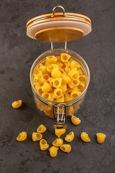 Une vue de face de pâtes sèches italiennes crues jaune à l'intérieur bol isolé sur le noir