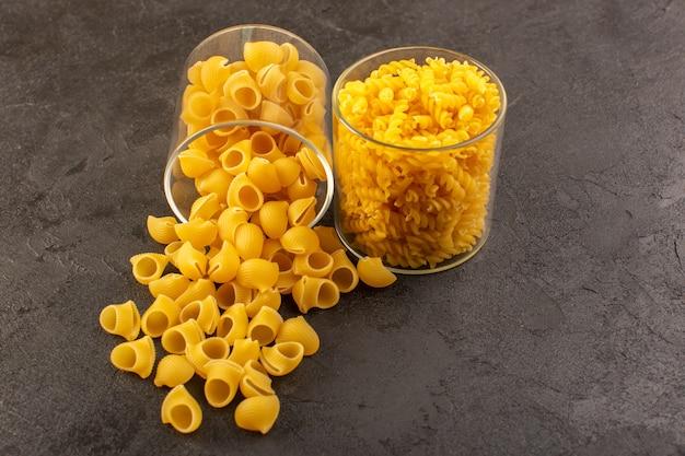 Une vue de face pâtes sèches italiennes crues jaunes à l'intérieur des bols isolés sur l'obscurité