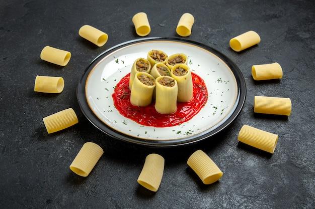 Vue de face des pâtes avec de la viande et de la sauce tomate sur espace gris