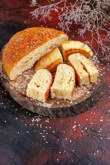 Vue de face de la pâtisserie sucrée coupée en morceaux sur le fond sombre