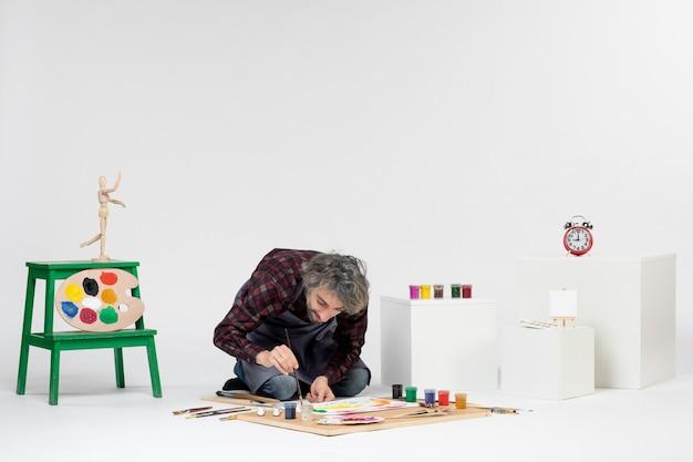 Vue de face peintre masculin dessinant des images avec des peintures sur blanc travail artiste couleur dessiner peinture art photo