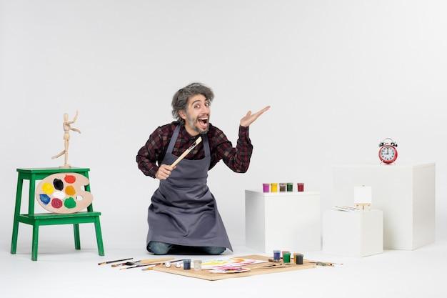 Vue de face peintre masculin à l'intérieur de la pièce avec des peintures et des pinceaux pour dessiner sur fond blanc art dessiner homme artiste peinture image couleur