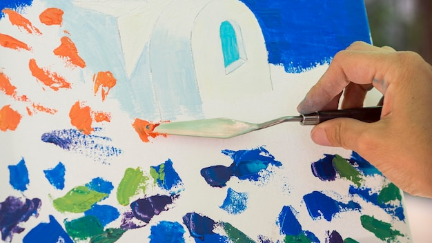 Vue de face de la peinture à la main à l'aide de l'outil
