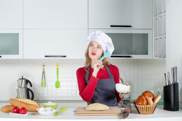 Vue de face pensant femme blonde en chapeau de cuisinier et tablier beurrant du pain dans la cuisine