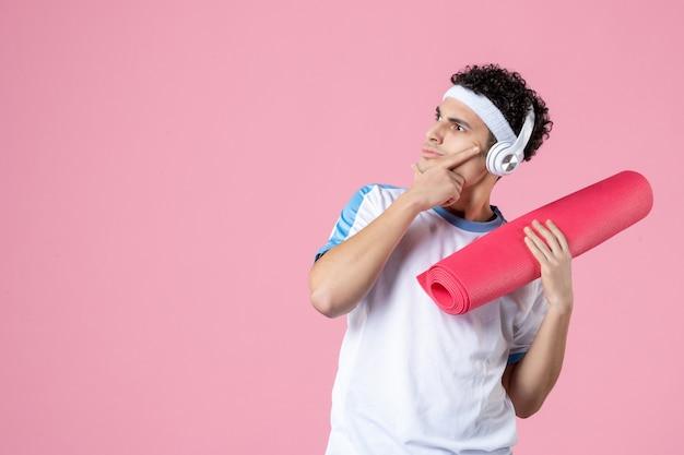 Vue de face pensant jeune homme en vêtements de sport avec tapis de yoga et écouteurs