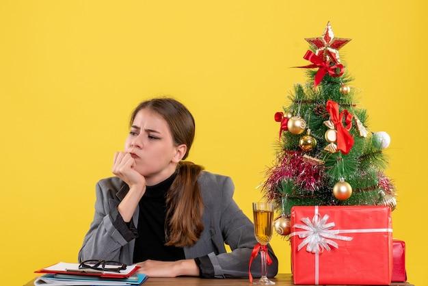 Vue de face pensant jolie fille assise au bureau arbre de noël et cadeaux cocktail