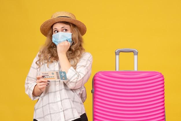 Vue de face de la pensée jeune femme portant un masque montrant billet et debout près de son sac rose sur jaune