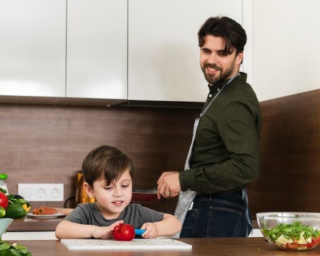 Vue de face père et fils cuisinant