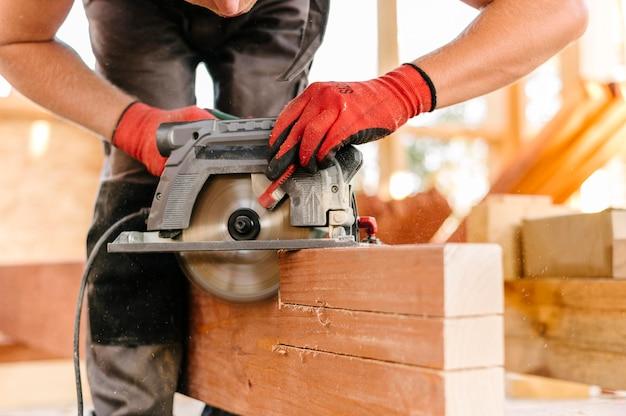 Vue de face personne à l'aide d'une machine-outil pour couper le bois