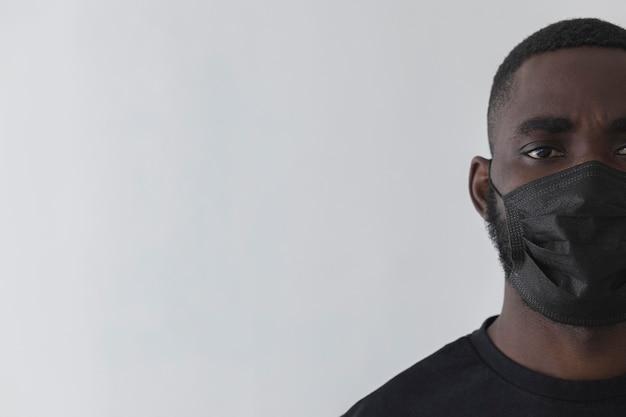 Vue de face personne noire portant un espace de copie de masque