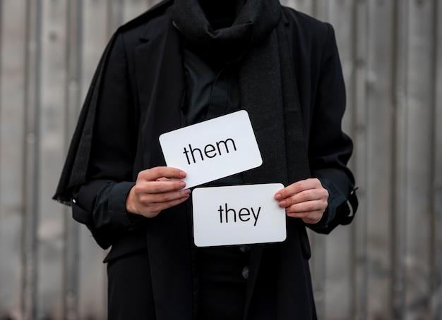 Vue de face personne non binaire tenant des cartes de pronoms