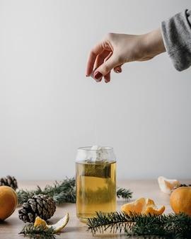 Vue de face personne prenant le sachet de thé en pot