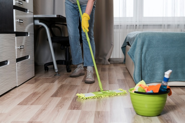Vue de face de la personne qui essuie le sol dans la chambre