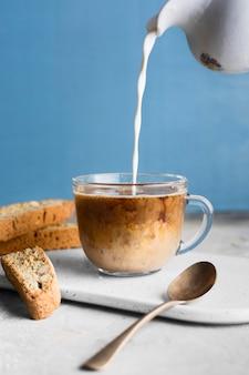 Vue de face personne verser le lait en verre avec café
