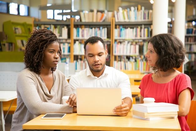 Vue de face de personnes réfléchies travaillant à la bibliothèque
