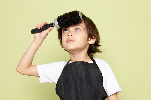 Une vue de face petit coiffeur adorable enfant en cape noire posant
