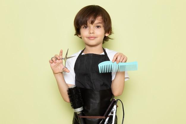 Une vue de face petit coiffeur adorable enfant en cape noire tenant une brosse et des ciseaux