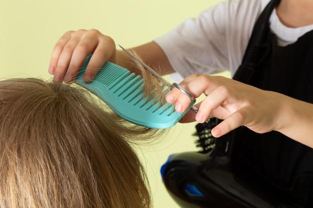 Une vue de face petit coiffeur adorable enfant travaillant avec la coiffure des garçons
