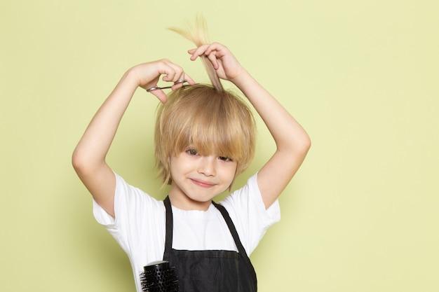 Une vue de face petit coiffeur mignon adorable gamin blond avec des ciseaux