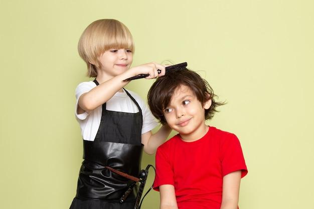 Une vue de face petit coiffeur mignon enfant adorable travaillant