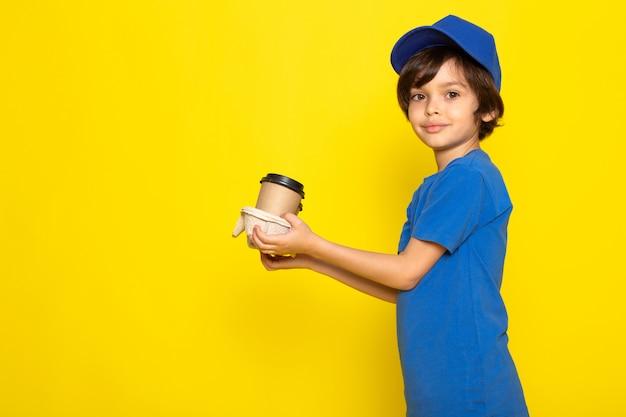 Une vue de face petit coursier mignon en t-shirt bleu casquette bleue tenant des tasses à café