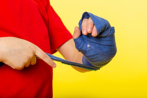 Une vue de face petit enfant garçon attachant sa main avec du tissu bleu pour la boxe en t-shirt rouge sur le mur jaune