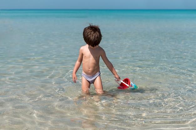 Vue de face d'un petit enfant qui joue dans l'eau