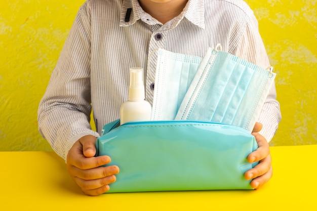Vue de face petit enfant tenant boîte de stylo bleu avec spray et masques sur surface jaune