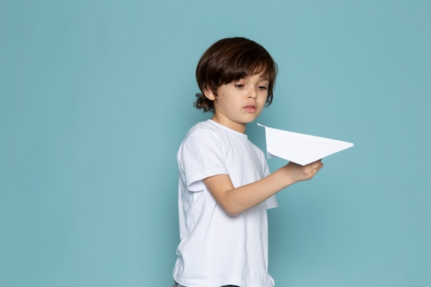Vue de face petit garçon jouant avec un avion en papier sur le bureau bleu