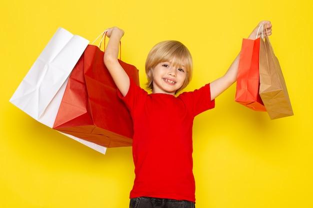 Une vue de face petit garçon mignon en jeans t-shirt rouge posant