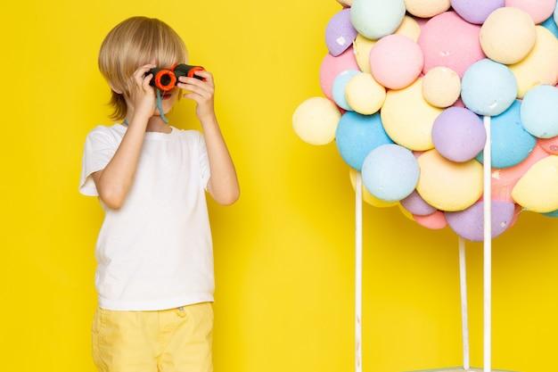 Vue de face petit garçon mignon en t-shirt blanc avec des ballons à air colorés sur un bureau jaune