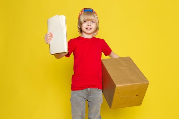Une vue de face petit garçon en t-shirt rouge casquette colorée et un jean gris tenant la boîte sur le fond jaune