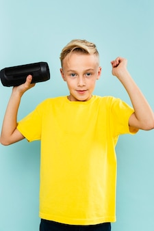 Vue de face, petit garçon tenant une cassette