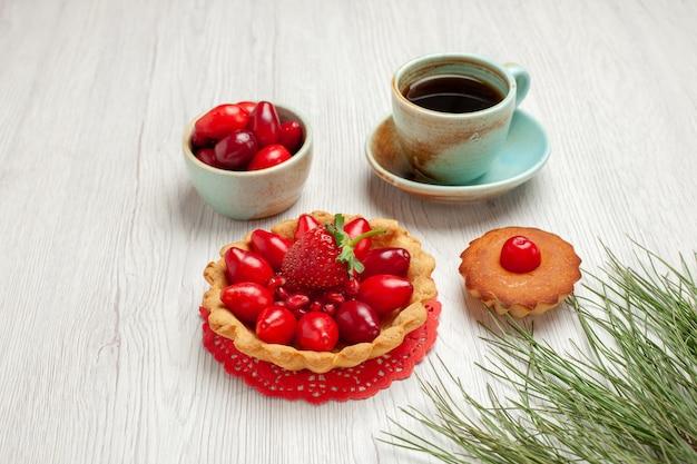 Vue de face petit gâteau aux fruits et tasse de thé sur un bureau blanc thé couleur dessert fruits