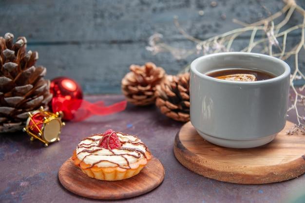 Vue de face petit gâteau crémeux avec une tasse de thé sur fond sombre biscuit à tarte gâteau au sucre sucré