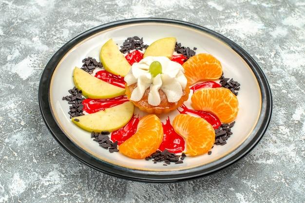 Vue de face petit gâteau avec des tranches de pommes et de mandarines à l'intérieur de la plaque sur fond blanc gâteau aux fruits sucré biscuit biscuit au sucre