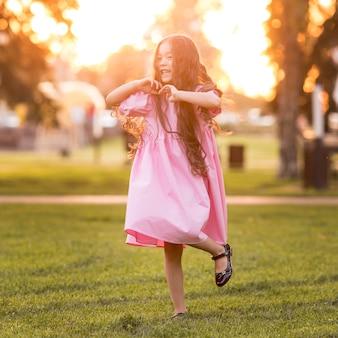 Vue de face petite fille asiatique aux cheveux longs marchant dans le parc
