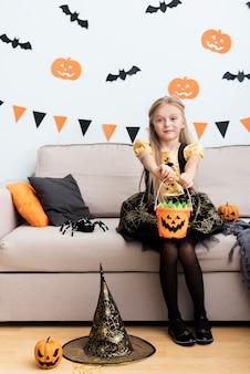 Vue de face de petite fille en costume de sorcière