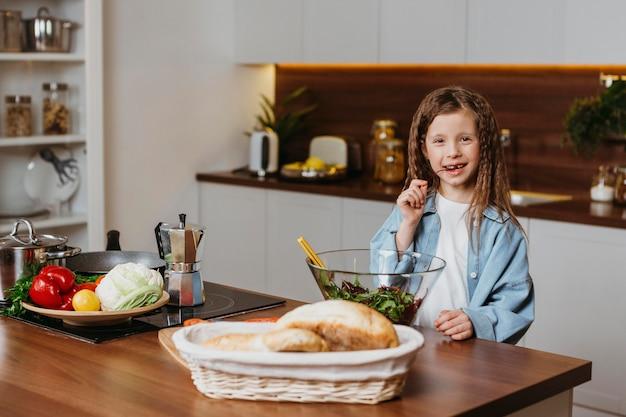 Vue de face de la petite fille dans la cuisine