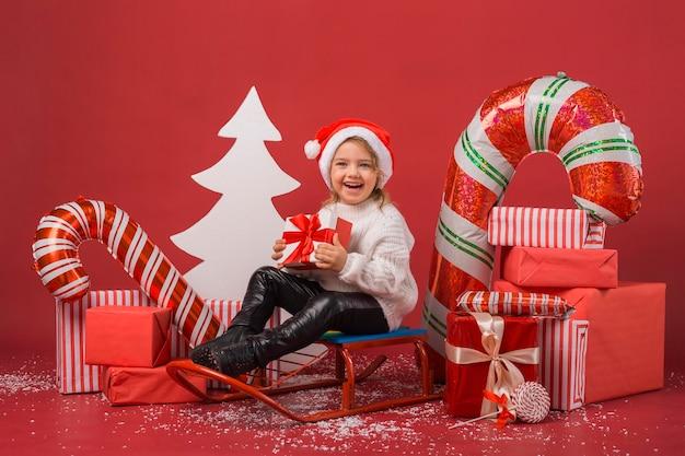 Vue de face petite fille entourée de cadeaux de noël et d'éléments