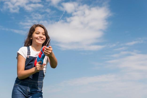 Vue de face, petite fille jouant avec un pistolet à eau à l'extérieur