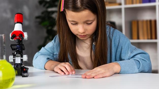 Vue de face de la petite fille avec microscope et tubes à essai