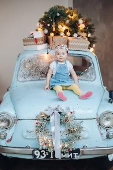 Vue de face de petite fille mignonne douce et à la mode, assise sur une voiture rétro bleue décorée pour noël.