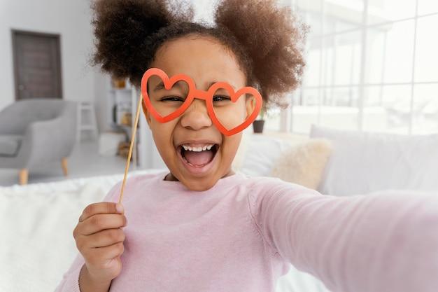 Vue de face de la petite fille prenant selfie à la maison