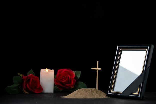 Vue de face de la petite tombe avec bougie et roses rouges sur fond noir