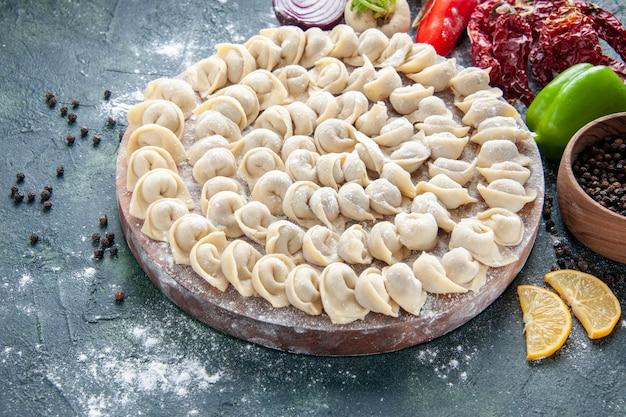 Vue de face de petites boulettes crues avec de la farine et des légumes sur une surface sombre