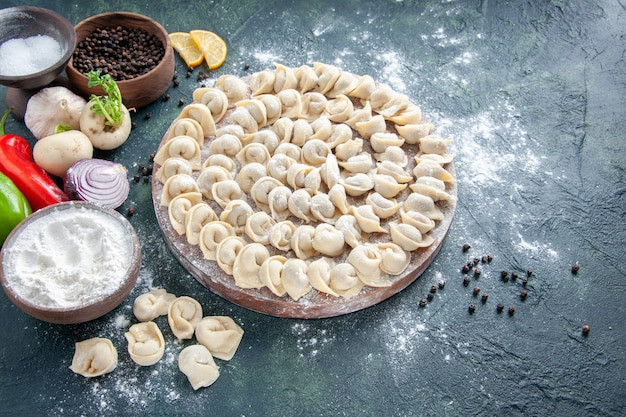 Vue de face petites boulettes crues avec de la farine sur une surface sombre
